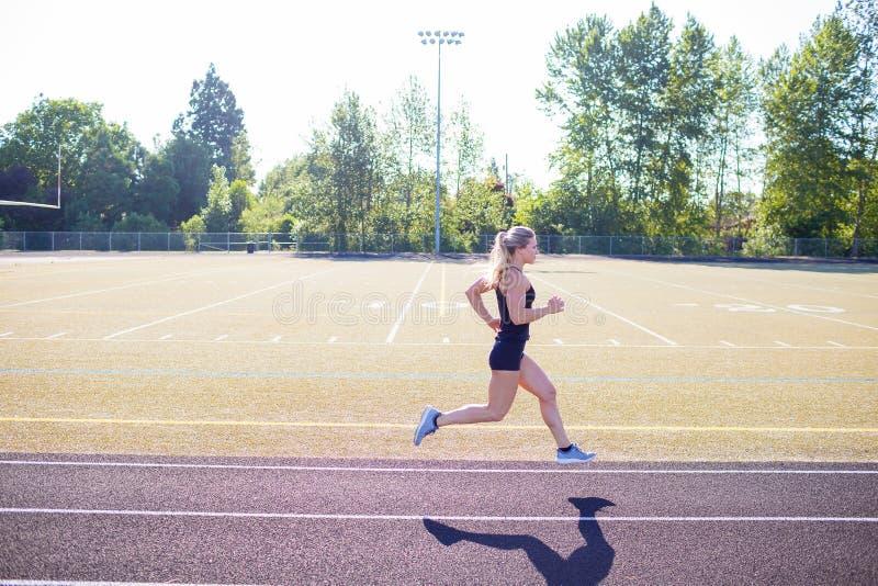 Молодая спортсменка разрабатывая на следе стоковое фото