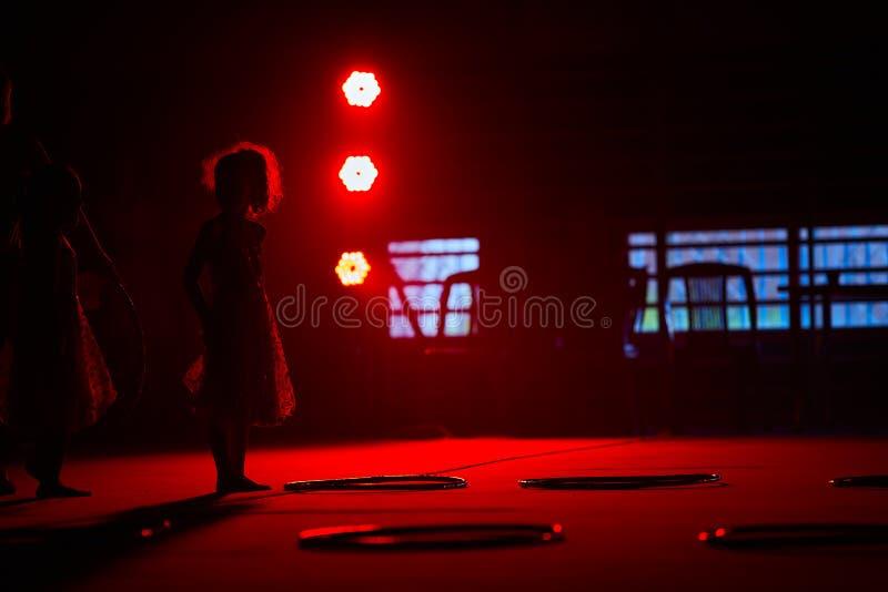 Молодая спортсменка с обручем подготавливает выполнить циркаческие элементы в красном сценарном свете стоковые фотографии rf