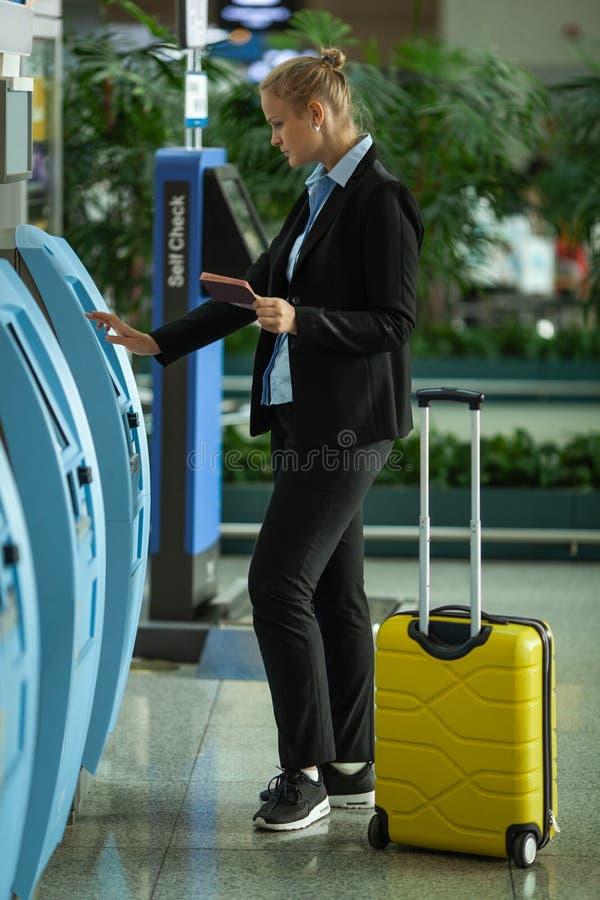 Молодая справедливая с волосами женщина в аэропорте около само- терминала проверки стоковые фото