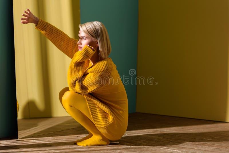 молодая стильная женщина в желтый сидеть свитера и колготков стоковая фотография rf