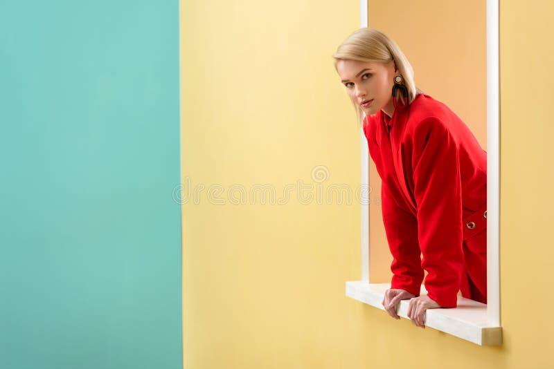 молодая стильная женщина в красном костюме смотря вне стоковая фотография rf