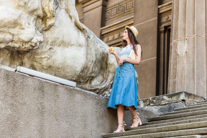молодая стильная женщина в шляпе со свежим положением яблока на шагах стоковая фотография rf