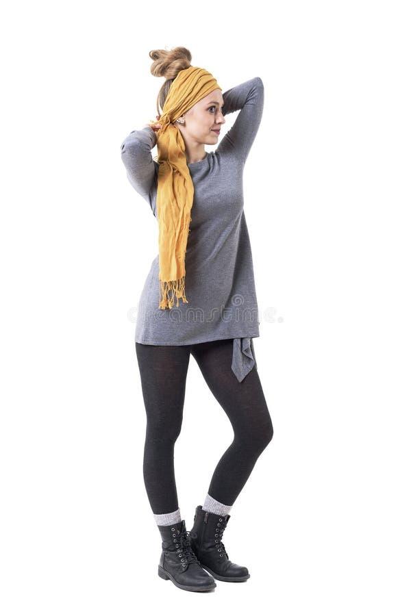 Молодая стильная уникальная девушка с плюшкой волос делая желтый тюрбан с банданой смотря зеркало стоковая фотография rf