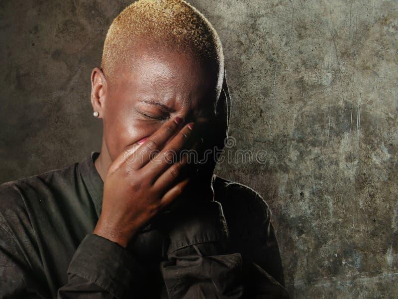 Молодая стильная унылая и подавленная афро американская чернокожая женщина плача в стороне заволакивания отчаяния с руками чувств стоковое фото