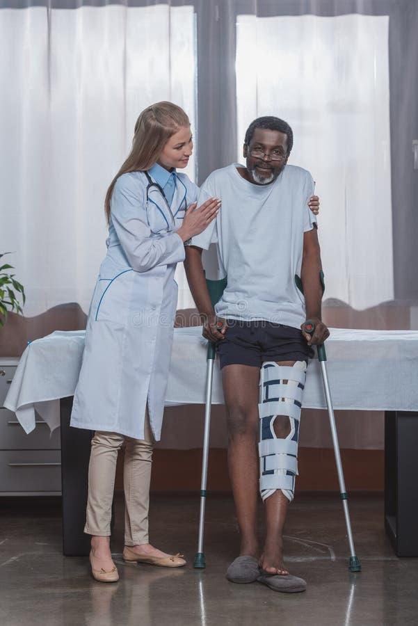 Молодая стойка порции доктора до Афро-американского пациента с расчалкой ноги стоковые фото