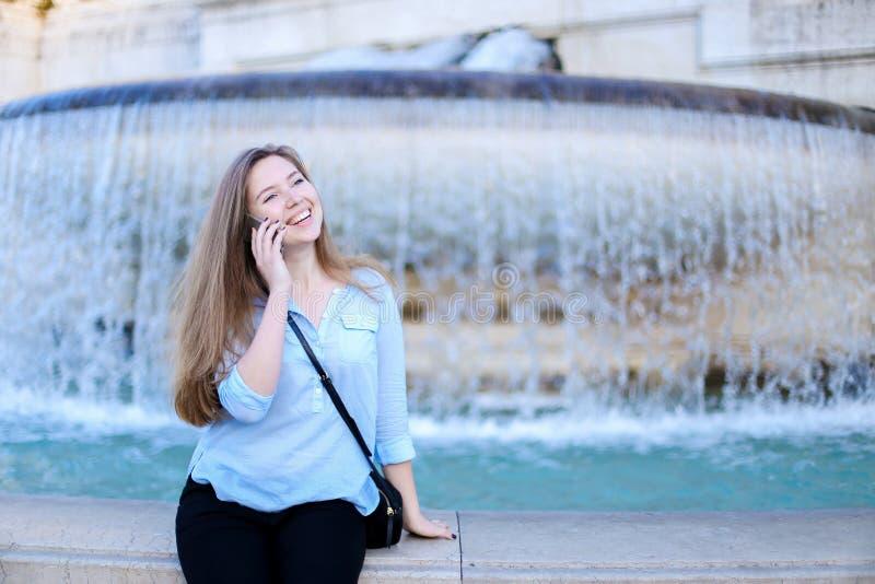 Молодая студентка говоря smartphone в предпосылке фонтана Trevi стоковое изображение