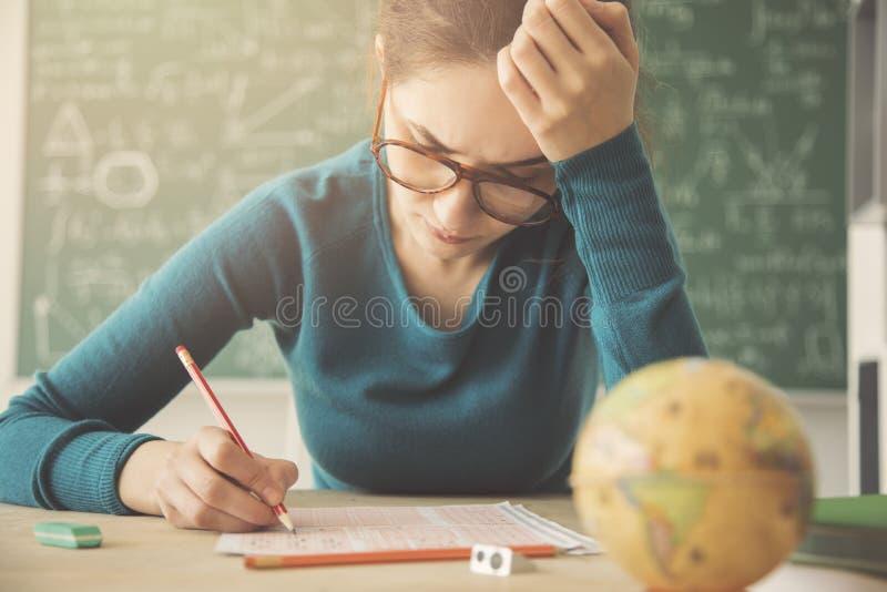 Молодая студентка имея рассмотрение стоковые фото