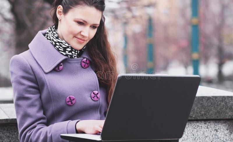 Молодая студентка используя его компьтер-книжку сидя на стенде в парке города стоковые изображения