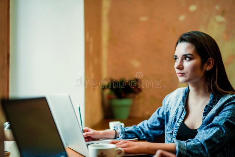 Молодая студентка сидит около окна с ноутбуком и взгляда через окно стоковые изображения rf