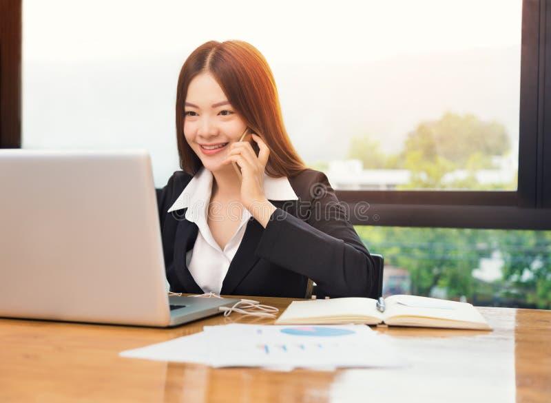 Молодая счастливая азиатская бизнес-леди говоря на ее телефоне пока работа стоковые изображения rf
