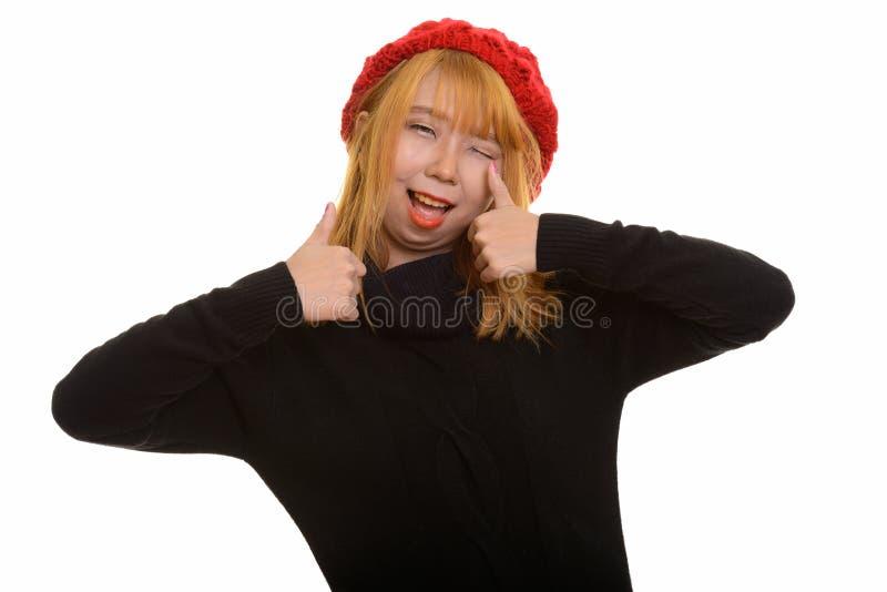 Молодая счастливая азиатская женщина усмехаясь и давая большие пальцы руки вверх пока winki стоковая фотография