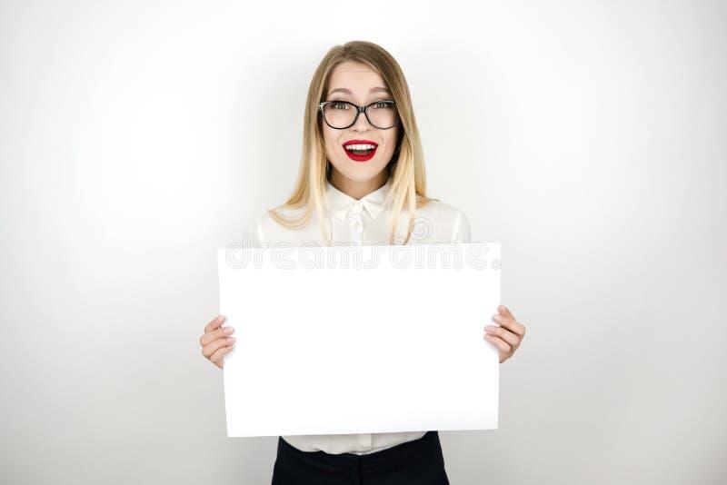 Молодая счастливая бизнес-леди в eyeglasses держа чистый лист бумаги для изолированного объявлением белого космоса предпосылки стоковое изображение rf