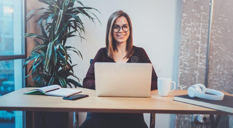 Молодая счастливая девушка используя передвижную компьтер-книжку для смотреть новое решение дела во время процесса работы на офис стоковое фото rf