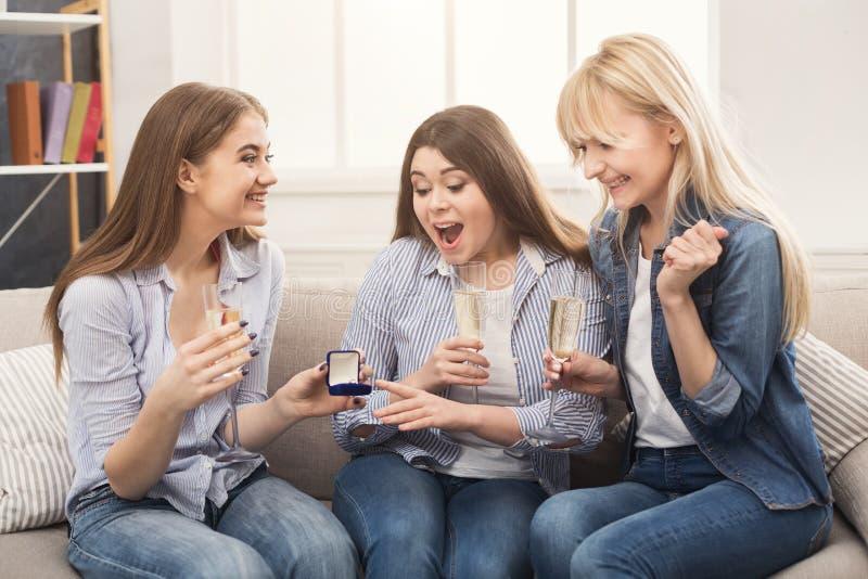 Молодая счастливая девушка показывая ее кольцо предложения к удивленным подругам стоковые изображения rf
