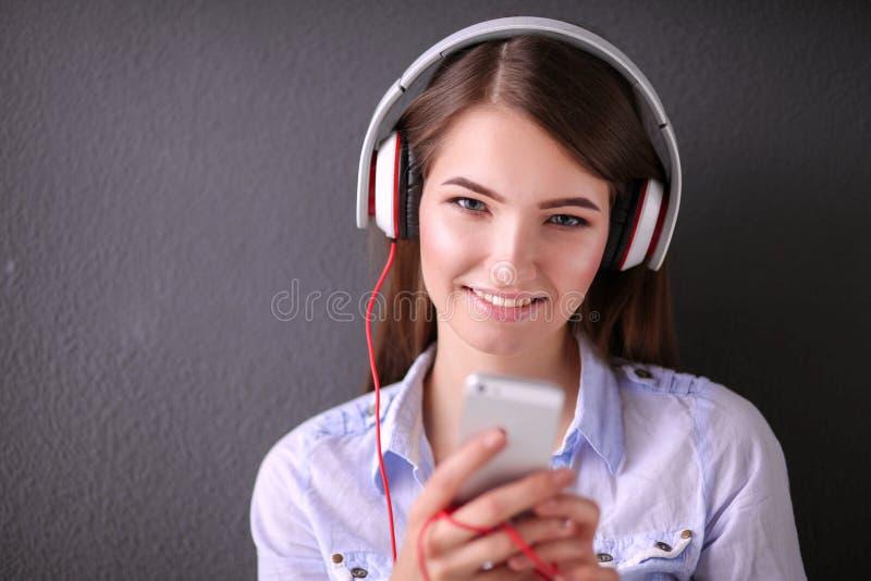 Молодая счастливая девушка сидя на поле и слушая музыке стоковая фотография