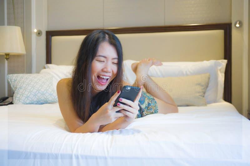 Молодая счастливая довольно азиатская корейская женщина дома или гостиничный номер лежа на кровати ослабили усмехаться используя  стоковые фотографии rf