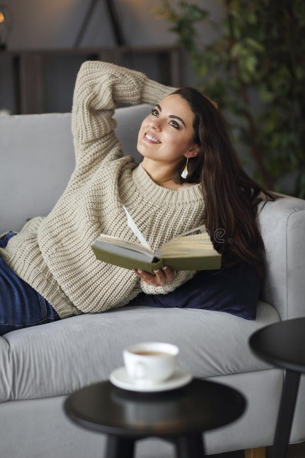 Молодая счастливая женщина брюнета со свитером книги нося стоковое изображение
