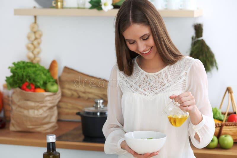Молодая счастливая женщина варя в кухне Здоровая еда, образ жизни и кулинарные концепции Доброе утро начинает со свежим стоковое фото rf