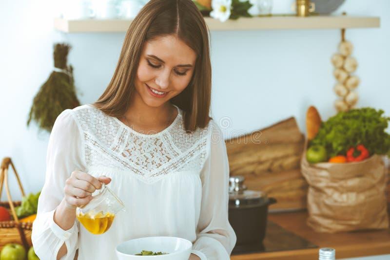 Молодая счастливая женщина варя в кухне Здоровая еда, образ жизни и кулинарные концепции Доброе утро начинает со свежим стоковые фото