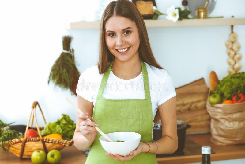 Молодая счастливая женщина варя в кухне Здоровая еда, образ жизни и кулинарные концепции Доброе утро начинает со свежим стоковая фотография rf