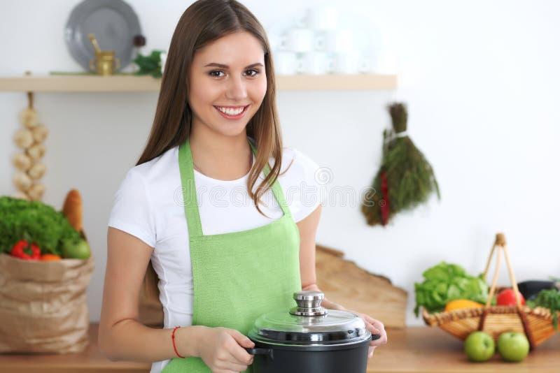 Молодая счастливая женщина варя суп в кухне Здоровая еда, образ жизни и кулинарная концепция студент девушки сь стоковое фото rf