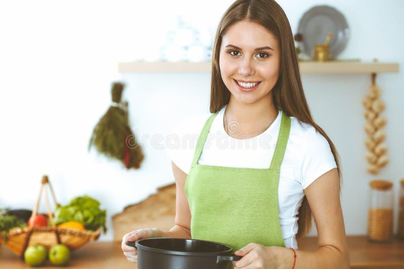 Молодая счастливая женщина варя суп в кухне Здоровая еда, образ жизни и кулинарная концепция Усмехаясь девушка студента стоковое фото rf