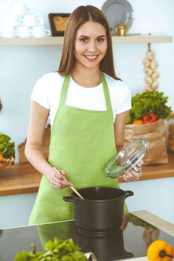 Молодая счастливая женщина варя суп в кухне Здоровая еда, образ жизни и кулинарная концепция Усмехаясь девушка студента стоковое фото