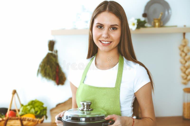 Молодая счастливая женщина варя суп в кухне Здоровая еда, образ жизни и кулинарная концепция Усмехаясь девушка студента стоковые фотографии rf