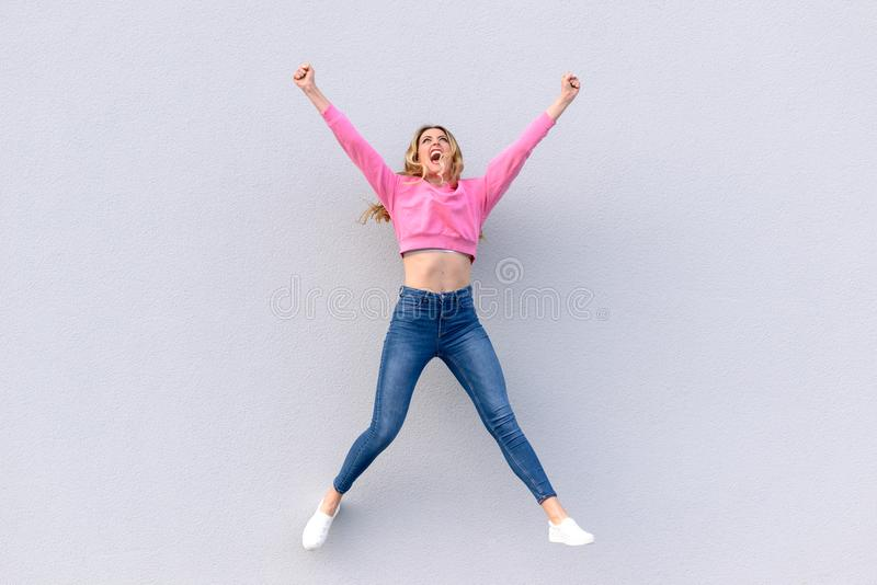 Молодая счастливая женщина в джинсах скача в воздух стоковое фото rf