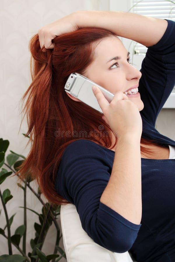 Молодая счастливая женщина говоря телефоном с смехом стоковые изображения rf