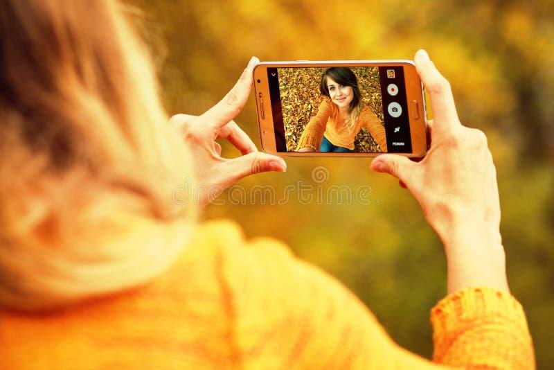 Молодая счастливая женщина делая selfie осени на smartphone для социального n стоковая фотография