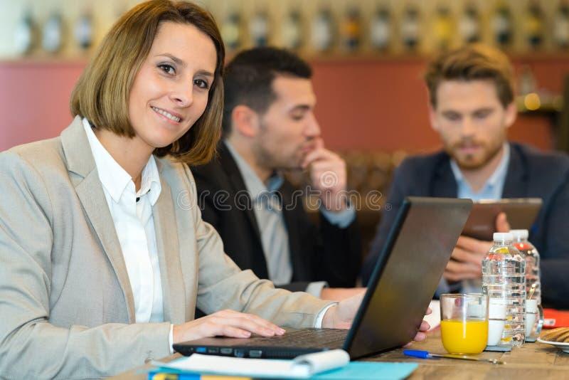 Молодая счастливая женщина используя тетрадь в кафе стоковые фото