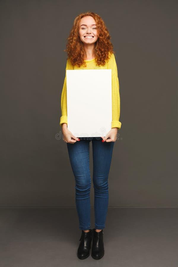 Молодая счастливая женщина с пустой белой бумагой стоковая фотография