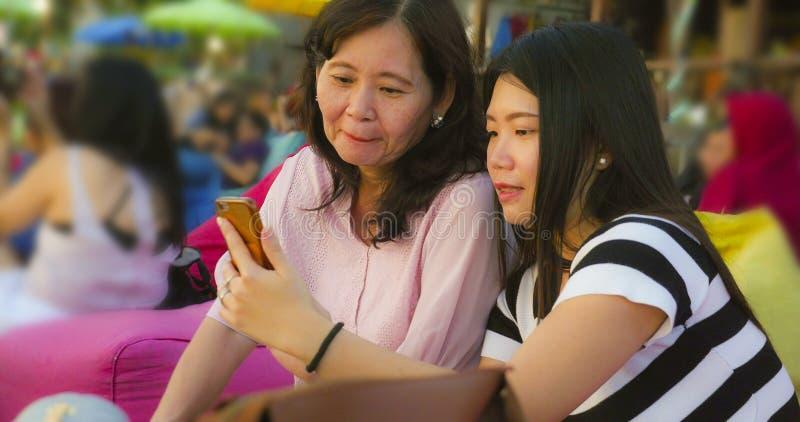 Молодая счастливая и довольно азиатская китайская девушка на пляже принимая фото selfie с ее матерью, зрелой женщиной 60s, наслаж стоковая фотография rf