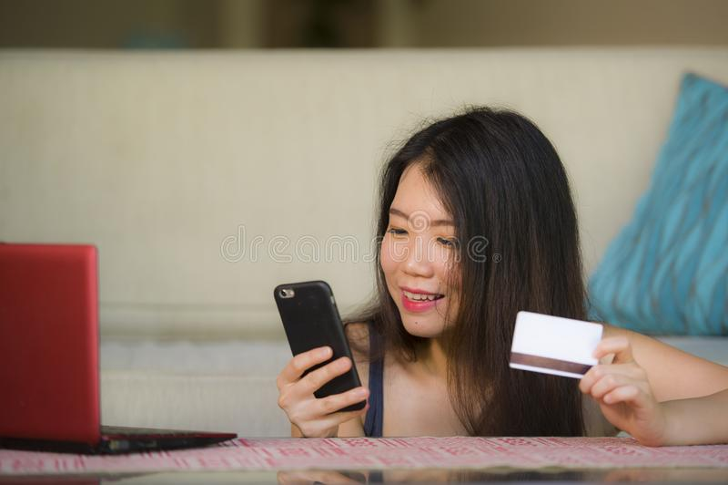 Молодая счастливая и красивая азиатская корейская женщина держа кредитную карточку используя мобильный телефон для банка интернет стоковая фотография