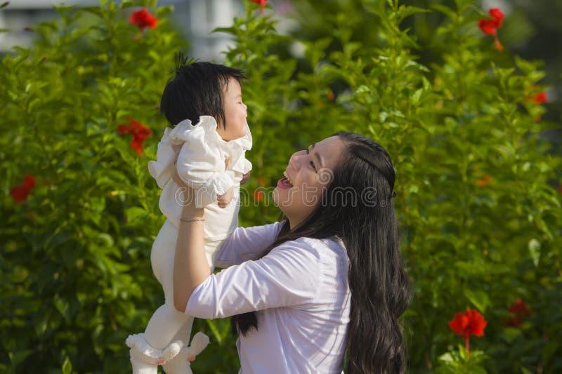 Молодая счастливая и милая азиатская китайская женщина наслаждаясь и играя с ее дочерью ребенка держа ее поднимая вверх в ее оруж стоковые изображения rf