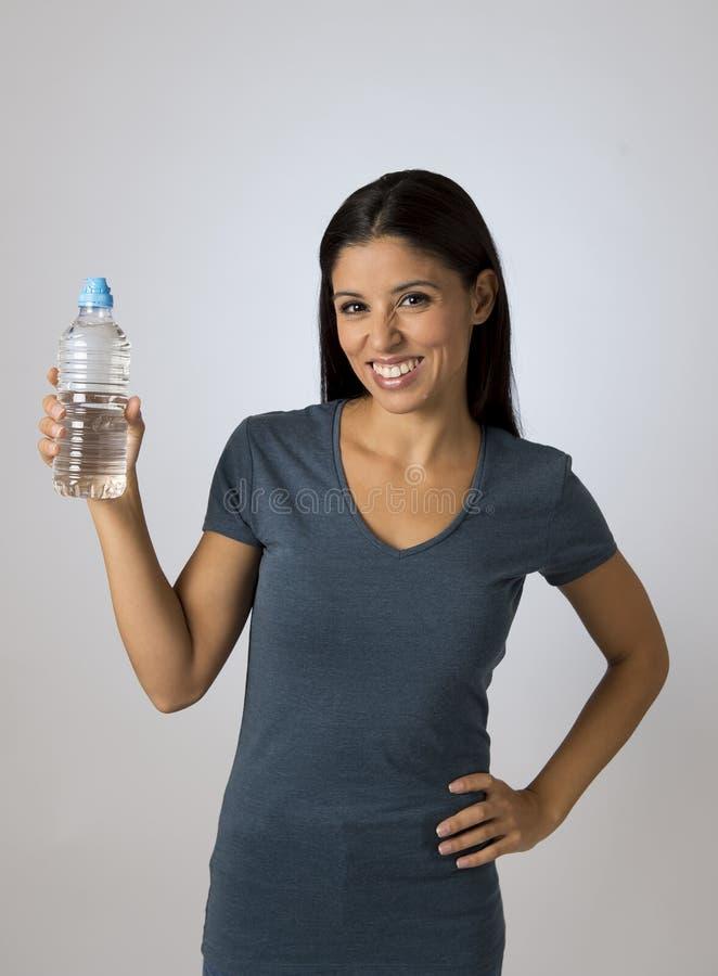 Молодая счастливая и привлекательная латинская женщина в вскользь одеждах держа усмехаться питьевой воды бутылки свежий стоковое фото