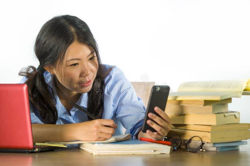 Молодая счастливая и успешная азиатская корейская девушка студента принимая фото автопортрета selfie с мобильным телефоном изучая стоковая фотография rf