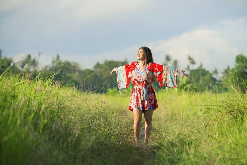 Молодая счастливая и шаловливая азиатская китайская женщина в красивом платье имея потеху наслаждаясь отклонением праздников на s стоковая фотография rf