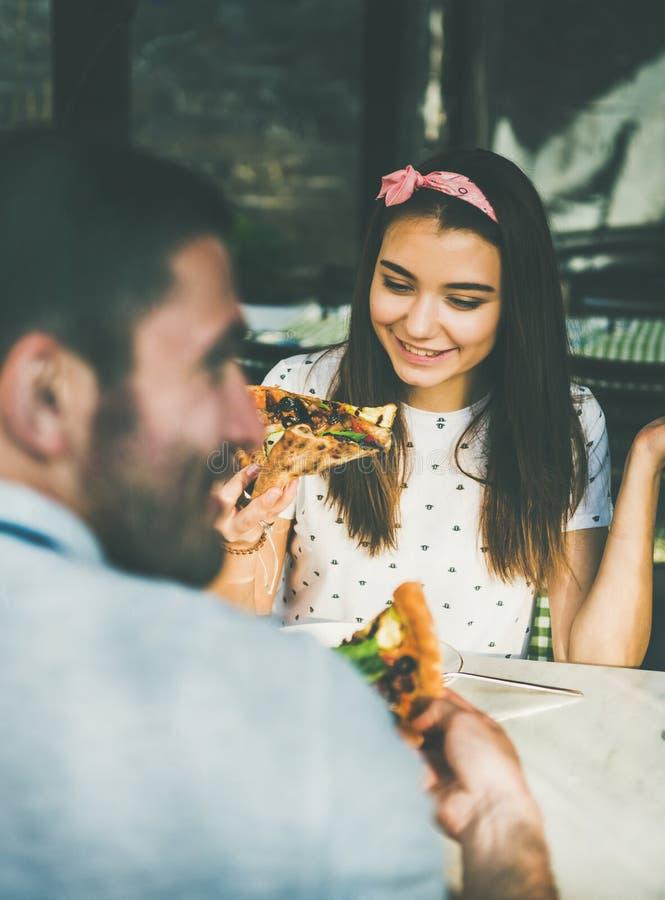 Молодая счастливая кавказская пара ест пиццу в кафе стоковые фото