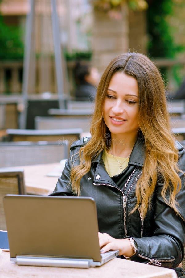 Молодая счастливая коммерсантка используя ноутбук в на открытом воздухе кафе стоковое изображение rf