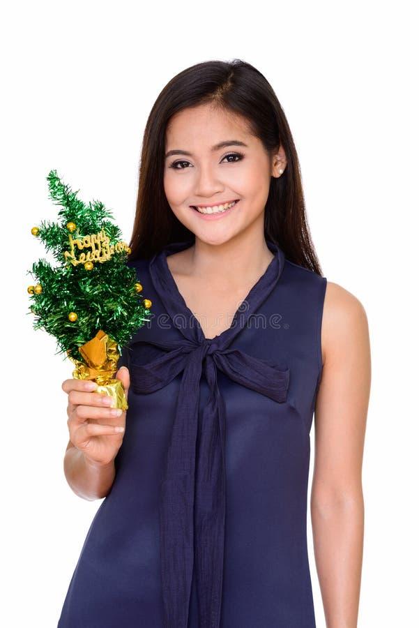 Молодая счастливая красивая азиатская женщина держа С Новым Годом! дерево стоковые изображения