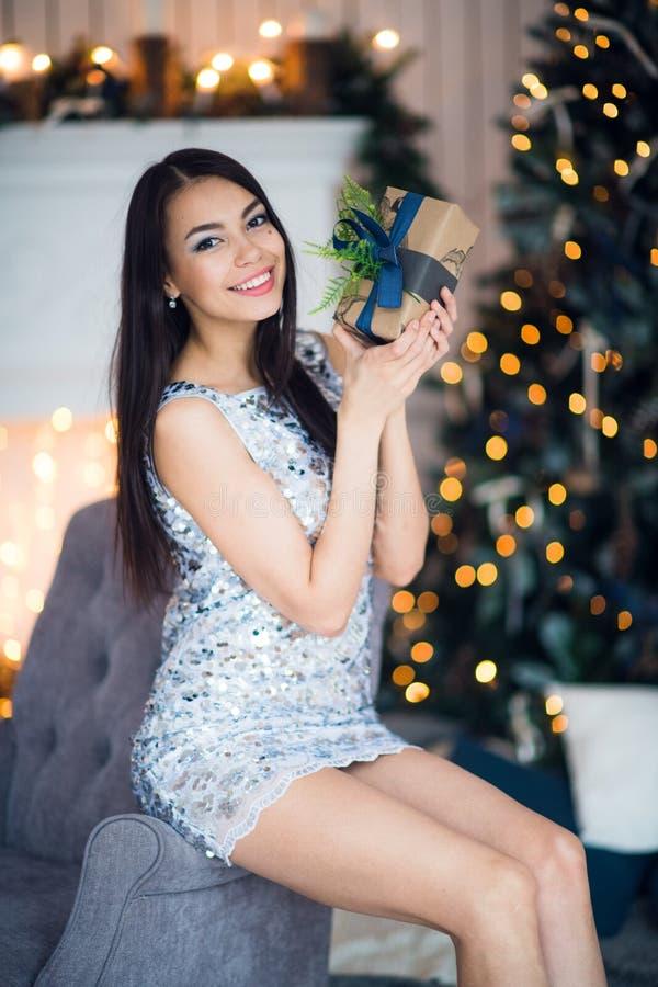 Молодая счастливая красивая женщина с подарочными коробками сидит около рождественской елки в комнате дома стоковые изображения rf