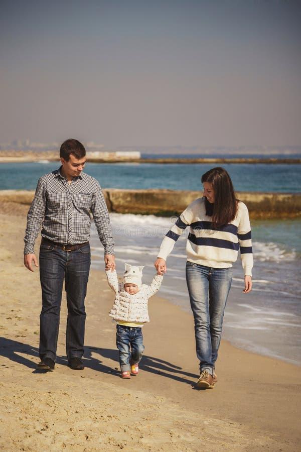Молодая счастливая любящая семья при малый ребенк в среднем, наслаждающся временем на пляже идя около океана, держа оружия, счаст стоковые фото