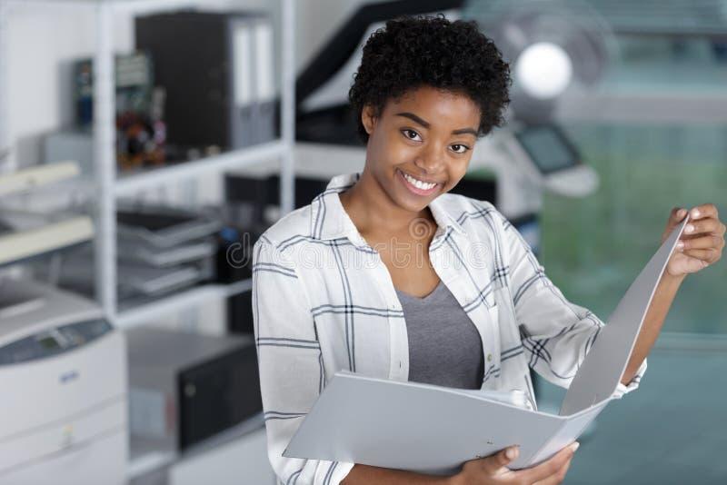 Молодая счастливая папка h женщины с документами в офисе стоковые изображения rf