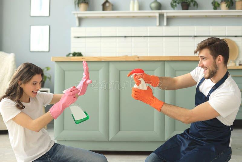 Молодая счастливая пара имеет потеху пока делающ чистку дома стоковые изображения rf