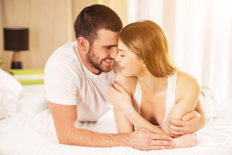 Молодая счастливая пара лежит в белой кровати дома стоковая фотография
