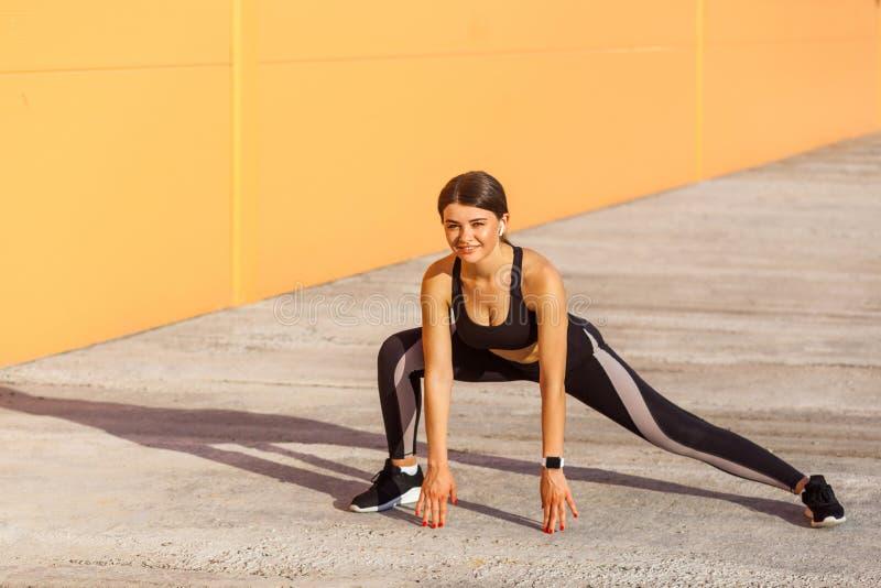 Молодая счастливая привлекательная женщина нося тренировки спорта черного sporwear практикуя в утре на улице, протягивая ноги, зу стоковое фото rf