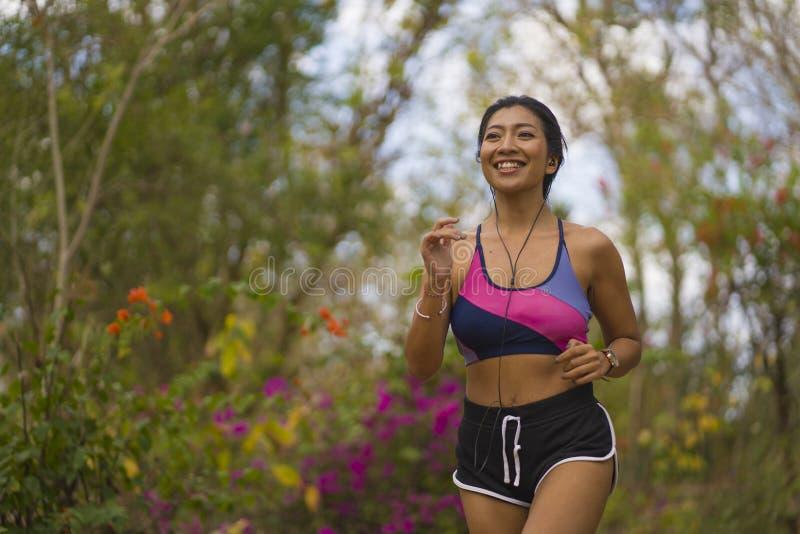 Молодая счастливая привлекательная и экзотическая азиатская индонезийская женщина бегуна в jogging разминке outdoors на природе с стоковые изображения