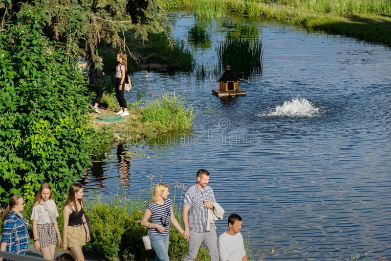 Молодая счастливая прогулка людей около красивого пруда в парке Zaryadye стоковое изображение